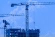 Construction cranes on a blue background. Building.
