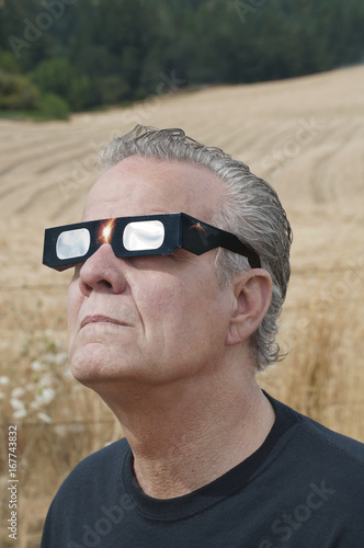 Man looking at the solar eclipse with eclipse glasses/Man viewing solar eclipse with solar glasses in country field/