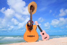 Sweet Brown Guitar And Pink Ukulele,hat, Headphones,football On Blue Sky And Beach Background