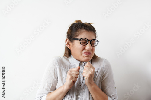 Photo Stressed young European employee or office worker in glasses and shirt screwing her mouth in disgust, aversion or antipathy, gesturing with hands