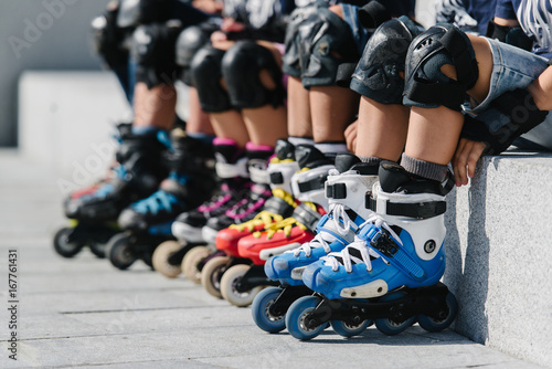 Feet of rollerbladers wearing inline roller skates sitting in outdoor skate park, Close up view of wheels befor skating