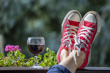 Red Sneakers On The Legs Of A Woman And A Glass Of Wine Against The Background Of Nature