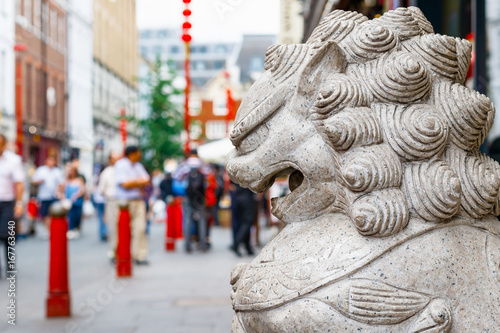 A guardian lion statue located in the crowded London Chinatown