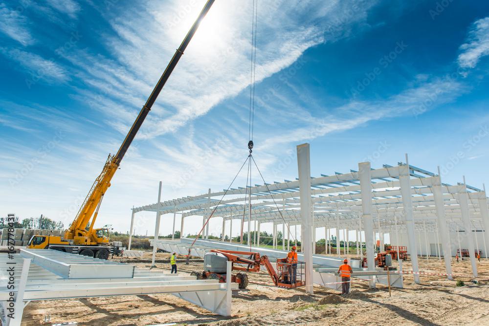 Fototapety, obrazy: Budowa hali produkcyjnej w fazie montażu konstrukcji stalowej szkieletu za pomocą dźwigu