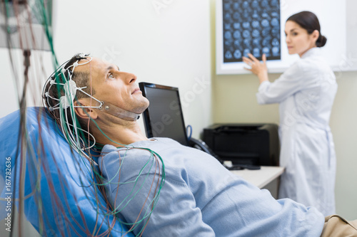 Obraz Female doctor carrying out electroencephalography of man - fototapety do salonu