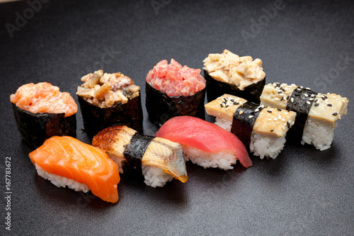 Fototapeta  Many different sushi on a black table, Japanese food