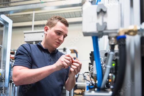 Factory worker repairing equipment