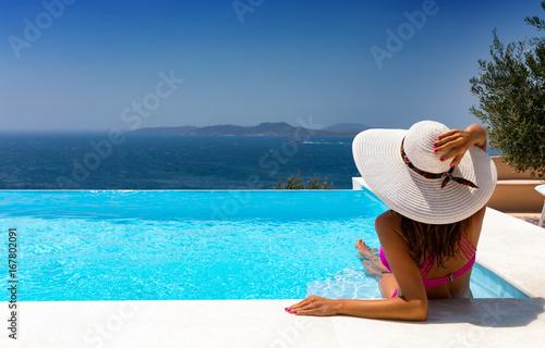 Attraktive Frau mit weißem Hut entspannt in einem Infinity Pool