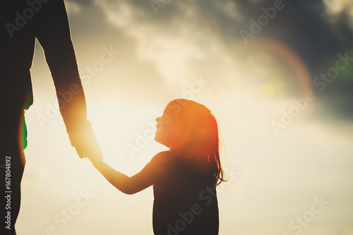 Fotografía  silhouette of little girl holding parent hand at sunset