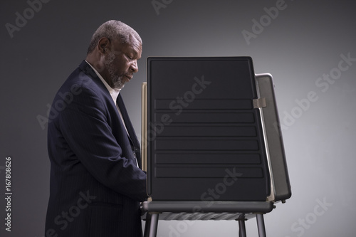 Fotografie, Tablou Portrait of a black man standing in a voting booth