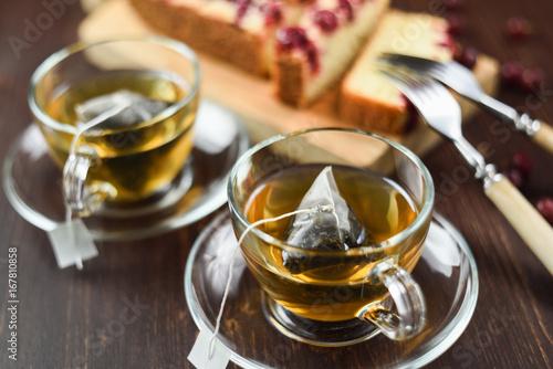 Zdjęcie XXL Zielona herbata parzona w torebkach z herbatą piramidalną w szklanych filiżankach i jagodowym cieście. Zdrowy napój