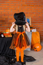 Portrait Of Small Girl In Orange Black Witch Halloween Costume .Happy Halloween Concept. Trick Or Treat
