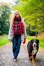 Woman Walking The Dog On Leash...