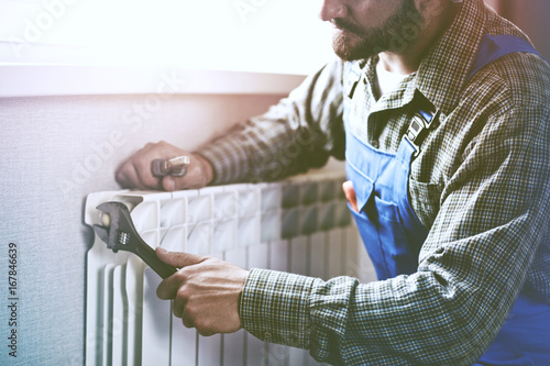 Fototapeta service man with wrench near radiator obraz