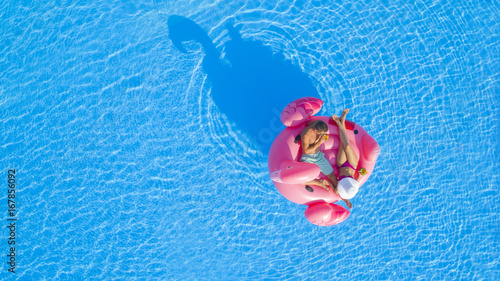 AERIAL TOP DOWN: Young man and woman drinking cocktails and relaxing while lying on fun inflatable pink flamingo floatie. Sexy couple in swimsuit sipping drinks, enjoying floating on sunny pool water