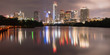 Panorama view of Downtown Austin, Texas, USA skylines reflection on the Colorado River at twilight. View from Ann and Roy Butler Hike-and-Bike Trail and boardwalk at Lady Bird Lake is on the left.