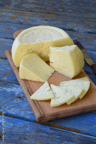 Fényképezés  young homemade cheese on a blue wooden background