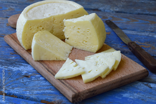 young homemade cheese on a blue wooden background Poster