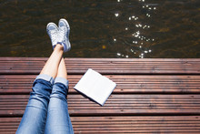 Woman Relaxing By A Lake With A Book. Reading And Summer Holiday Concept.