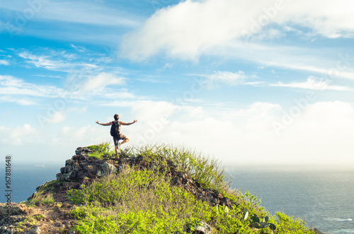 Fotobehang Ontspanning Man on a mountain striking a balance yoga pose feeling at peace with nature.