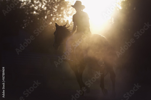 Fotografía  Silhouette of a woman riding a horse - sunset or sunrise, horizontal