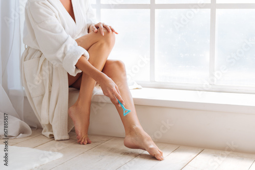 Healthy young woman holding blue razor