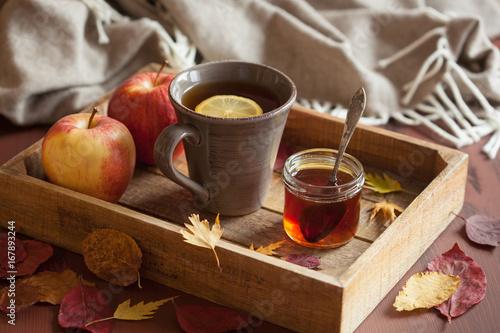 Photo sur Toile The hot lemon honey tea warming drink scarf cozy autumn leaves