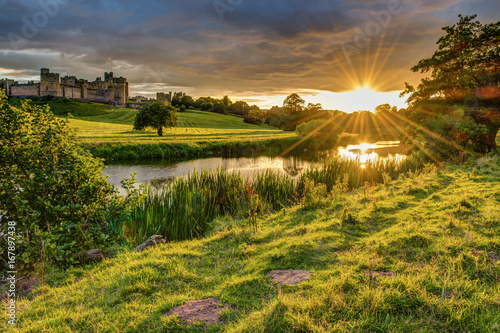 Photo sur Toile Miel Sunbeams over River Aln at Alnwick / The River Aln runs through Northumberland from Alnham to Alnmouth. Seen here below Alnwick Town and Castle on the skyline, as the sun goes down