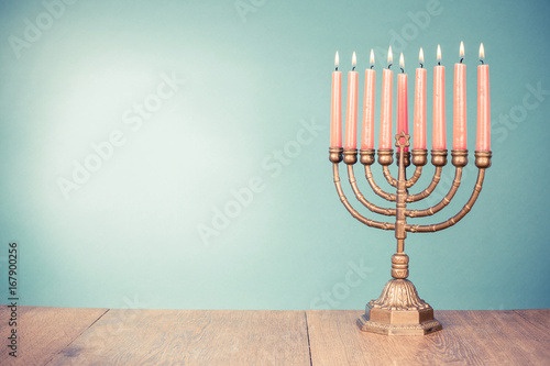 Photo Bronze Hanukkah menorah with burning candles for holiday card background