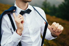 Man Poses In White Shirt With Suspenders