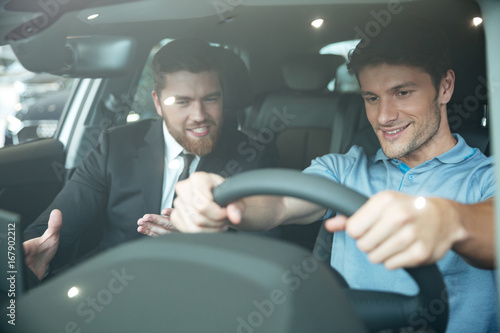 Fotografia, Obraz Professional young male dealer selling car to a customer