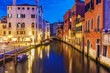 Venice cityscape at night with bright lights, Grand canal and floating boats.