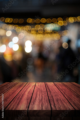 Fotografía  wooden table in front of abstract blurred background of lights