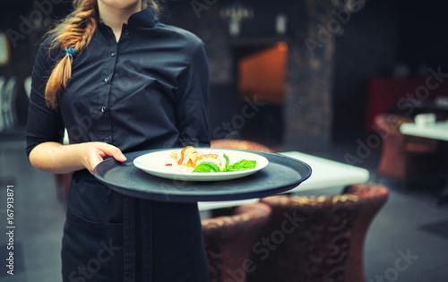 Zdjęcie XXL Kelnerzy niosący talerze z jedzeniem, w restauracji.