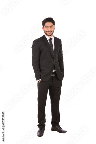 2a2d345bec Full length shot of a happy handsome young businessman with hand in pocket  smiling and looking to you, guy wearing black suit and black tie, isolated  on ...