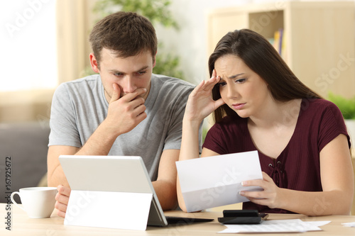 Fotografía  Worried couple reading together a letter