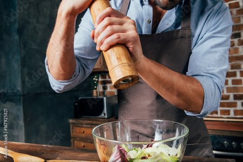 Fotografía  cropped shot of man adding pepper with mill into salad