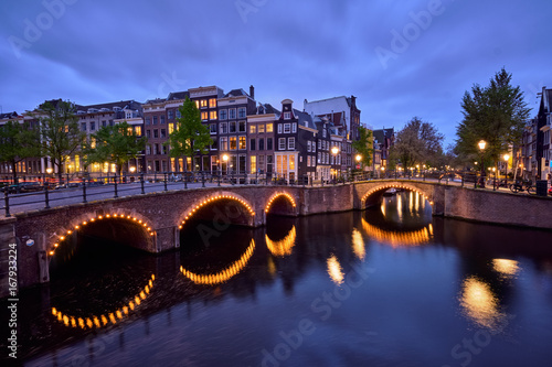Photo Amterdam canal, bridge and medieval houses in the evening