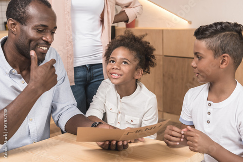 happy african-american family looking at menu list in cafe Poster