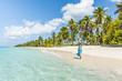 Canto de la Playa, Saona Island, East National Park (Parque Nacional del Este), Dominican Republic, Caribbean Sea. Beautiful woman on a palm-fringed beach (MR).