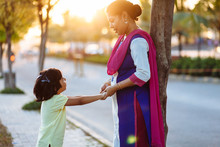 Little Girl Talking To Her Mother Standing On The Pavement