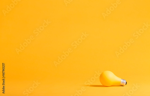 Photo  Yellow light bulb on a yellow background minimalist style
