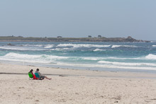 Couple Reading On Beach