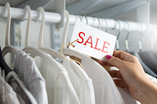 e3d10f76d6933 Female customer browsing clothes in a shop or outlet. Woman shopping for fashion  offer and