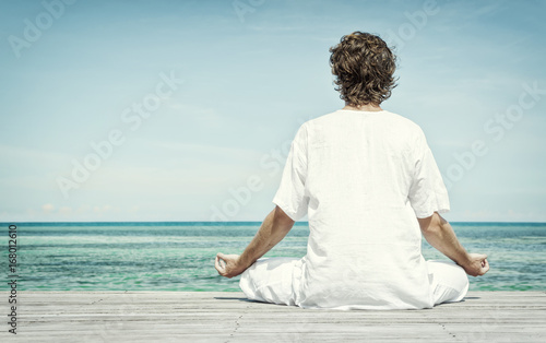 Printed kitchen splashbacks Artist KB Young man sitting in the lotus position and meditating on the beach close up