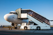 Passenger Jet Plane With Boarding Steps Vehicle On The Airport Apron Preparate For The Departure