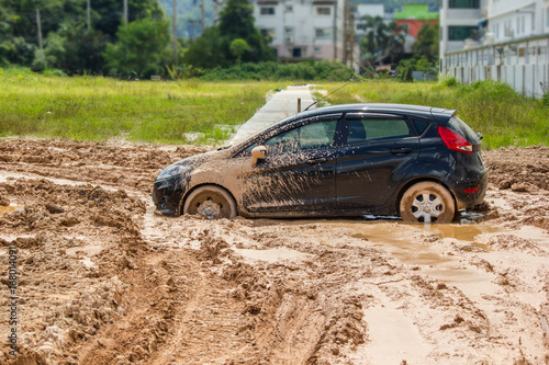 Fotografie, Obraz  The black car stuck in the mud. Can not fall out of the mud
