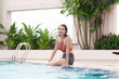 Portrait of a young asian woman sitting by pool with feet in water