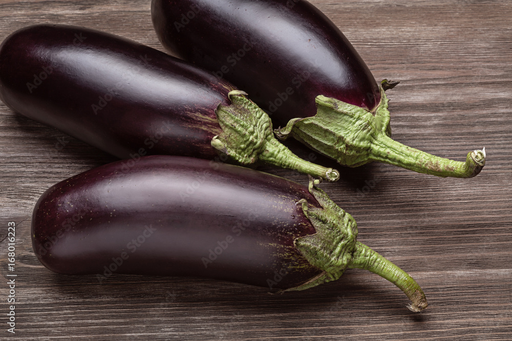 Three fresh eggplants on a wooden surface. Poster