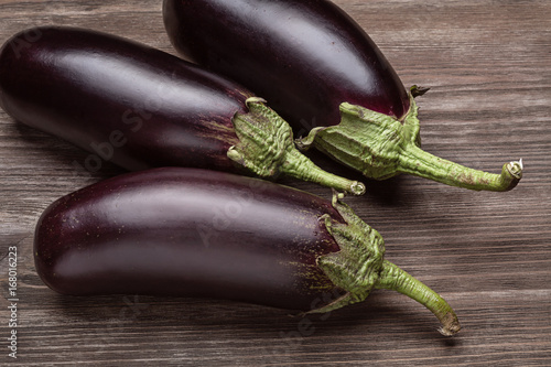 Foto  Three fresh eggplants on a wooden surface.